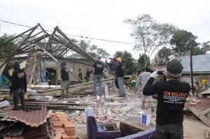 Relawan pemuda Miruek Aceh Besar sedang Merubuhkan rumah warga Wih Nongkal. (ist)