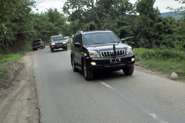 Serombongan kenderaan roda  mewah dengan nomor polisi BL 1 BF dengan kawalan ketat aparat keamanan melintas di kawasan Cot Panglima Bireuen menuju Gayo