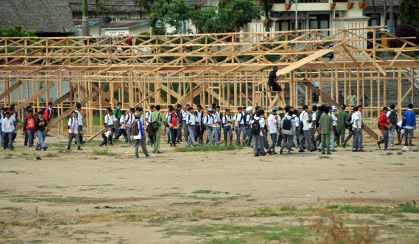 Siswa beranjak pulang, tukang bangunan sekolah sedang bekerja. (Win Aman)