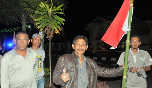 Bergotong royong, warga melakukan pemasangan bendera di jalan Yos Sudarso Takengon. (Kha A Zaghlul)