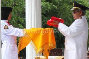 Gubernur Aceh dr Zaini Abdullah menyerahkan bendera merah Putih kepada anggota paskibraka.(LGco-aman.ZaiZa)