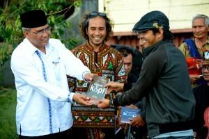 Seorang penulis puisi di buku antologi Puisi Secangkir Kopi, Mukhlis Muhdan menerima buku dari Bupati Aceh Tengah. (Munawardi)