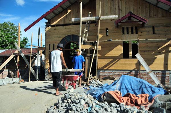 Sejumlah warga sedang bekerja membangun rumah dengan konstruksi kayu. (LGco_Kha A Zaghlul)