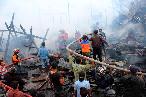 Petugas Damkar Aceh Tengah bersama anggota TNI dan   masrakat bergotongroyong memadamkan api. (LGco : Salman Yoga S)