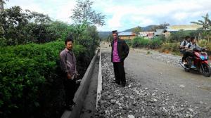 Foto: Camat Atu Lintang, Junaidi bersama seorang warga Pantan Damar memperhatikan drainase sepanjang 500 meter yang dibangun menggunakan dana desa