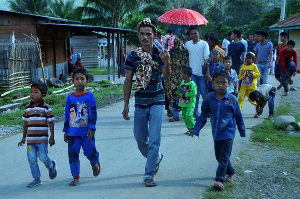 Berbondong-bondong berjalan kaki dari kediaman pengantin wanita dipimpin oleh seorang pria. (LGco_Khalis)
