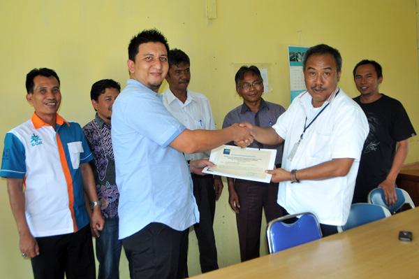 Direktur PT. Meukat Komoditi Gayo, Iwannitosa (kiri) menerima dokumen izin pasar lelang dari Kabid