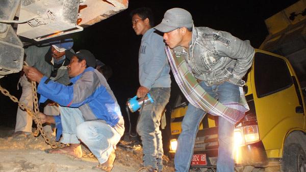 Pemasangan rantai untuk menarik truk yang terjebak  di tanah labi. (LGco_Khalis)
