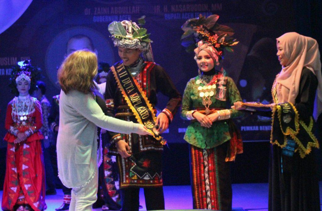 Penyematan selempang untuk satu juara oleh perwakilan juri, Mrs. Judith